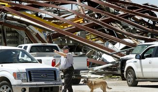 A police officer offers directions to a driver leaving a heavily damaged supply yard for Cactus Drilling Co. in El Reno, Okla., on Saturday, June 1, 2013. Employee David Stottemyre was working in the lot when a tornado took aim at the plant. Mr. Stottemyre ran inside the large supply storage building and took shelter as the twister passed over, leaving the building in a twisted pile of steel and metal. He was not injured. (AP Photo/The Oklahoman, Jim Beckel)