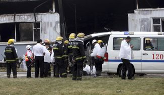 Firefighters and medical staff prepare to remove body bags that appears to contain the bodies of those killed by a fire at a poultry processing plant in northeast China's Jilin province's Mishazi township on Monday, June 3, 2013. The massive fire broke out at the poultry plant early Monday, trapping workers inside a cluttered slaughterhouse and killing over a hundred people, reports and officials said. (AP Photo)