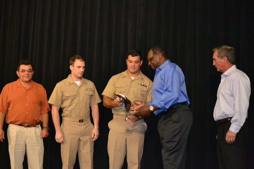 Washington Redskins fullback Eric Kettani, center, talks with Redskins running backs coach Bobby Turner after a pinning ceremony at Redskins Park in Ashburn, Va., in which Kettani was promoted to lieutenant in the Navy Reserves. Also pictured are Mounir Kettani, Eric's father, Navy Lt. Matthew Harmon and Redskins coach Mike Shanahan (The Washington Redskins)