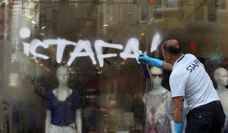 A man cleans graffiti reading ''Resign'' from a storefront on Istiklal Street, Istanbul's main shopping strip, Monday, June 3, 2013. The demonstrations that grew out of anger over excessive police force have spiraled into Turkey's biggest anti-government demonstrations in years, challenging Prime Minister's Recep Tayyip Erdogan power. (AP Photo/Thanassis Stavrakis)