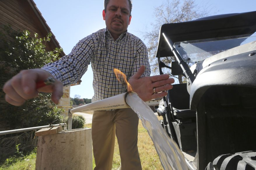 **FILE** Steve Lipsky demonstrates how his well water ignites when he puts a flame to the flowing well spigot outside his family's home in rural Parker County near Weatherford, Texas, on Nov. 26, 2012. The U.S. Environmental Protection Agency had evidence a gas company's drilling operation contaminated Lipsky's drinking water with explosive methane, and possibly cancer-causing chemicals, but withdrew its enforcement action, leaving the family with no useable water supply, according to a report obtained by the Associated Press. (Associated Press)