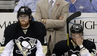 Pittsburgh Penguins coach Dan Bylsma stands behind James Neal (18) and Jussi Jokinen (36) during the third period of Game 2 of the NHL hockey Stanley Cup playoffs Eastern Conference finals against the Boston Bruins, in Pittsburgh on Monday, June 3, 2013. The Bruins won 6-1. (AP Photo/Gene J. Puskar)