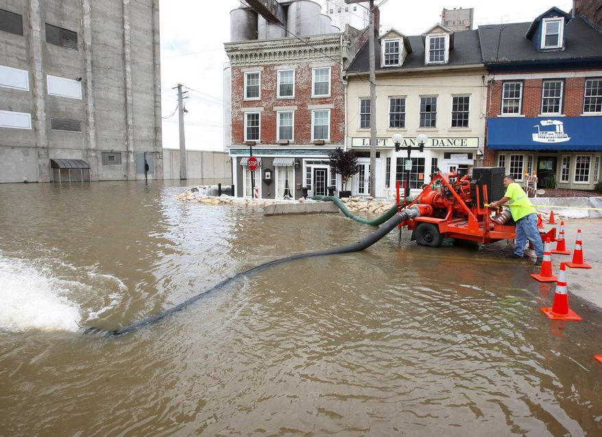 An Alton, Ill., Public Works employee checks on one of several large pumps being used to keep Mississippi River floodwaters at bay in downtown Alton, Ill., Monday, June 3, 2013. (AP Photo/The Telegraph, John Badman)