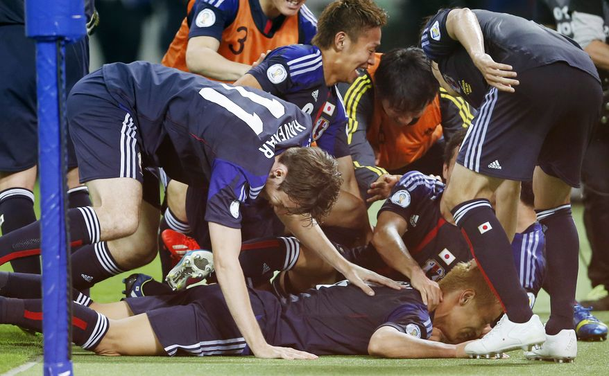 Japan's Keisuke Honda, bottom, celebrates with his teammates after he scored on a penalty kick during their Asian zone Group B qualifying soccer match against Australia for the 2014 World Cup at Saitama Stadium in Saitama, near Tokyo, Tuesday, June 4, 2013. Japan became the first team to qualify for the World Cup, tying Australia 1-1 Tuesday night on Honda's penalty kick in the first minute of second-half stoppage time. (AP Photo/Koji Sasahara)