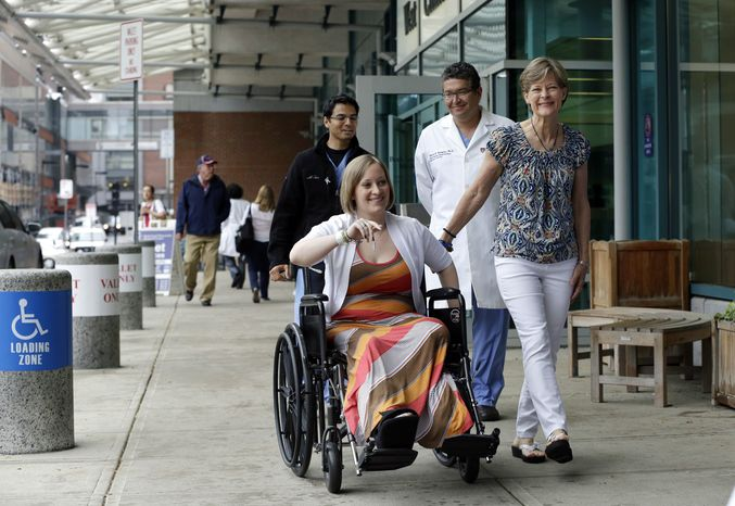 Boston Marathon bombing survivor Erika Brannock, 29, a Baltimore area preschool teacher who lost a leg, is accompanied by her mother, Carol Downing, right, as she is released from Beth Israel Deaconess Medical Center in Boston, Monday, June 3, 2013. Brannock and her sister, Nicole Gross, were waiting at the finish line for their mother to finish the race when the bombs went off. Walking behind are Dr. Alok Gupta, left, and Dr. Edward Rodriguez. (AP Photo/Elise Amendola)