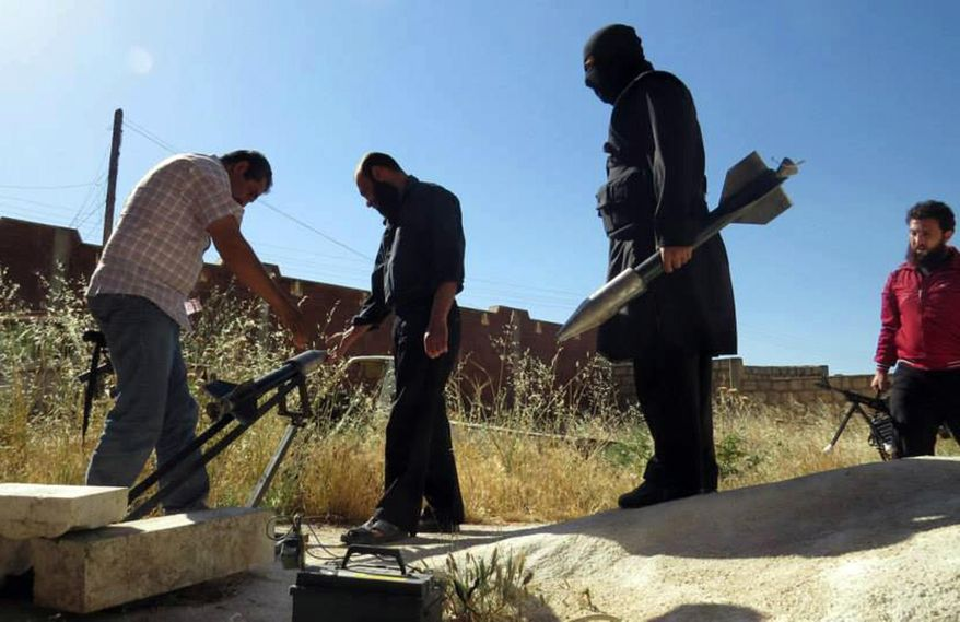 ** FILE ** This citizen journalism image provided by Edlib News Network, ENN, which has been authenticated based on its contents and other AP reporting, shows Syrian rebels preparing to fire locally made rockets, in Idlib province, northern Syria, Tuesday, June 4, 2013. (Associated Press)