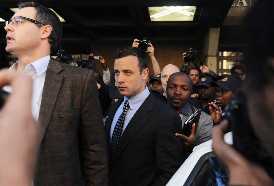 Oscar Pistorius, center, leaves the magistrates court in Pretoria, South Africa, Tuesday, June 4, 2013. Pistorius is accused of the shooting death of his girlfriend Reeva Steenkamp on Valentine's Day, Feb 14. The case has been postponed until Aug. 19. (AP Photo)