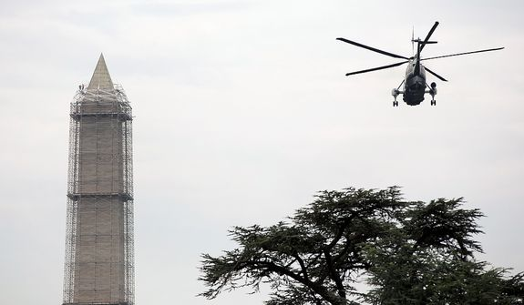 "Marine One, with President Barack Obama aboard, flies past the Washington Monument as workers build scaffolding to the top, Thursday, May 9, 2013, in Washington, to make repairs to the 555-foot marble obelisk that was damaged in the August 2011 earthquake. President Obama is en route to Texas, as part of his ìMiddle Class Jobs & Opportunity Tours."" (AP Photo/Carolyn Kaster)"