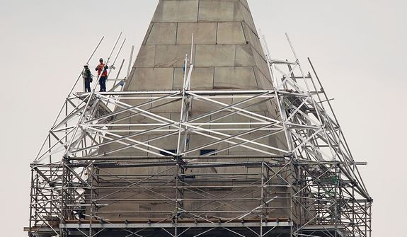 Scaffolding rises to the top of the Washington Monument, Thursday, May 9, 2013, in Washington, so craftsmen can make repairs to the 555-foot marble obelisk that was damaged in the August 2011 earthquake. (AP Photo/Carolyn Kaster)