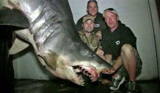 Fisherman pose with a mako shark they caught off the coast of Huntington beach, California. (Image: KTLA news)