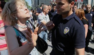 "A Turkish woman argues with riot police officers and ask them to not use tear gas against protesters, saying ""no more gas, please,"" at the main Kizilay Square near the office of Turkish Prime Minister, Recep Tayyip Erdogan, in Ankara, Turkey, Tuesday, June 4, 2013. Protests, the biggest Turkey has seen in recent years, were sparked by a police crackdown of a peaceful sit-in to prevent the demolition of a park in Istanbul. (AP Photo/Burhan Ozbilici)"