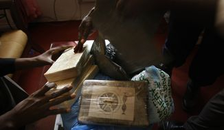 **FILE** Bags of confiscated cocaine are shown at the office of the Guinean drug enforcement agency in Conakry, Guinea, on March 11, 2009. (Associated Press)