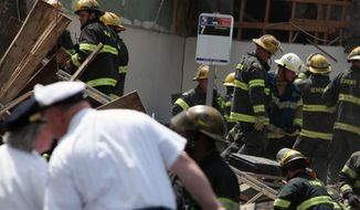 Emergency personnel respond June 5, 2013, to a building collapse in downtown Philadelphia, where the city fire commissioner says as many as eight to 10 people are believed trapped in the rubble. (Associated Press)