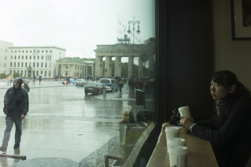 **FILE** A woman from China sits in a cafe and looks out of the window at Pariser Platz square with the Brandenburg Gate in background in Berlin on May 22, 2013. (Associated Press)