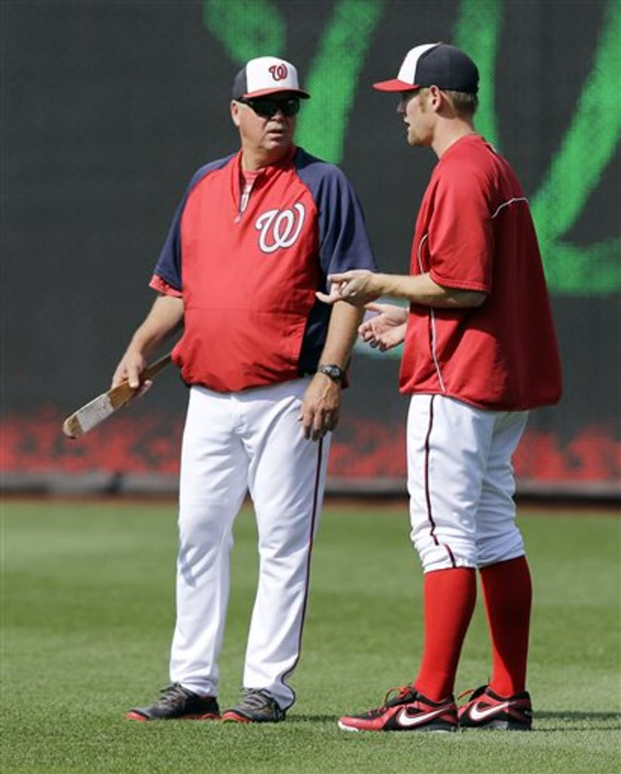 Washington Nationals pitching coach Steve McCatty, left, talks with starting pitcher Stephen Strasburg before a baseball game against the New York Mets at Nationals Park Wednesday, June 5, 2013, in Washington. Strasburg has been placed on the disabled list. (AP Photo/Alex Brandon)