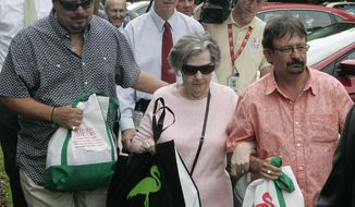 Powerball jackpot winner Gloria C. Mackenzie, 84, escorted by her son Scott (right), leaves Florida Lottery headquarters in Tallahassee, Fla., on Wednesday, June 5, 2013, after claiming a single lump-sum payment of about $370.9 million before taxes. (AP Photo/Steve Cannon)