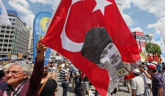 A Turkish protester waves a national flag with a poster of the nation's founder, Kemal Ataturk, as thousands of trade union members take part in a two-day march to Kizilay Square, the main city center in Ankara. (Associated Press)