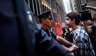 ** FILE ** A protester participating in the Occupy Wall Street protests faces a police officer while marching toward Wall Street, Oct. 14, 2011, in New York. (Associated Press)