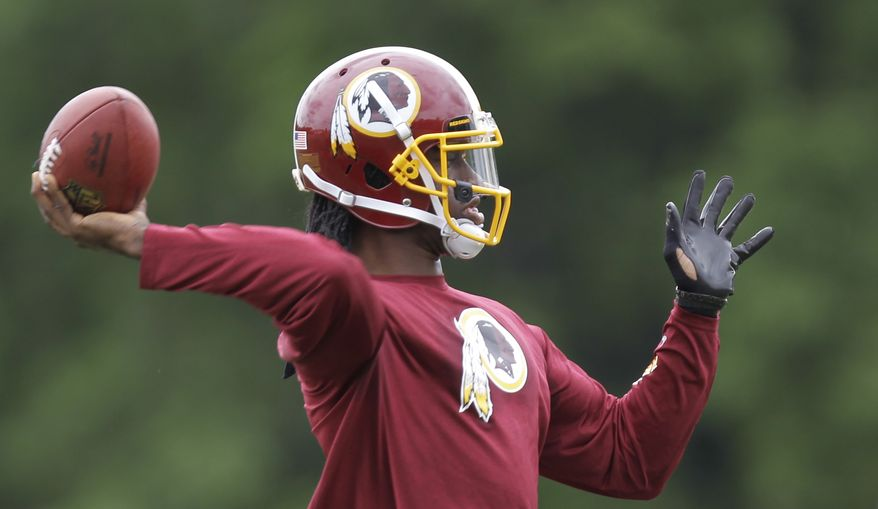 Washington Redskins quarterback Robert Griffin III throws a pass during team practice at Redskins Park, Thursday, June 6, 2013, in Ashburn, Va. (AP Photo/Luis M. Alvarez)
