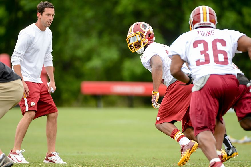 Washington Redskins offensive coordinator Kyle Shanahan, left, watches Washington Redskins tight end Niles Paul (84), center, run a route during a NFL football organized team activity at Redskins Park, Ashburn, Va., Thursday, June 6, 2013. (Andrew Harnik/The Washington Times)