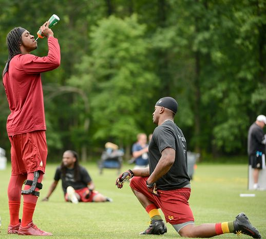 Washington Redskins quarterback Robert Griffin III (10), left, gets a drink from Washington Redskins tight end Fred Davis (83), right, before practice during a NFL football organized team activity at Redskins Park, Ashburn, Va., Thursday, June 6, 2013. (Andrew Harnik/The Washington Times)