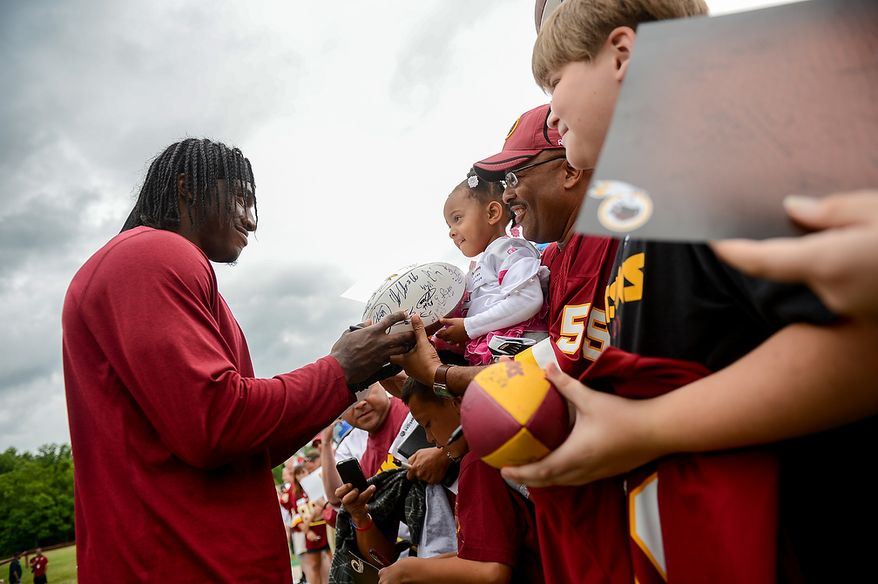 Washington Redskins quarterback Robert Griffin III (10) signs an autograph for Jordan Johnson, center, following a NFL football organized team activity at Redskins Park, Ashburn, Va., Thursday, June 6, 2013. (Andrew Harnik/The Washington Times)