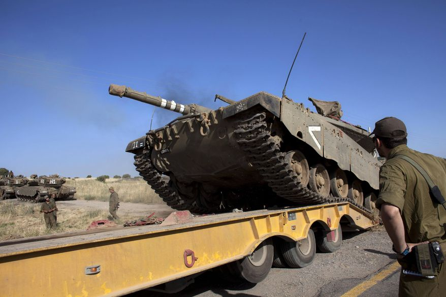 An Israeli tank is loaded onto a truck near the Quneitra crossing with Syria, Thursday, June 6, 2013. Syrian rebels on Thursday captured a crossing point along a cease-fire line with Israel in the contested Golan Heights, a development that could deepen Israeli concerns over the growing role of Islamic radicals in the civil war near its northern frontier.(AP Photo/Sebastian Scheiner)