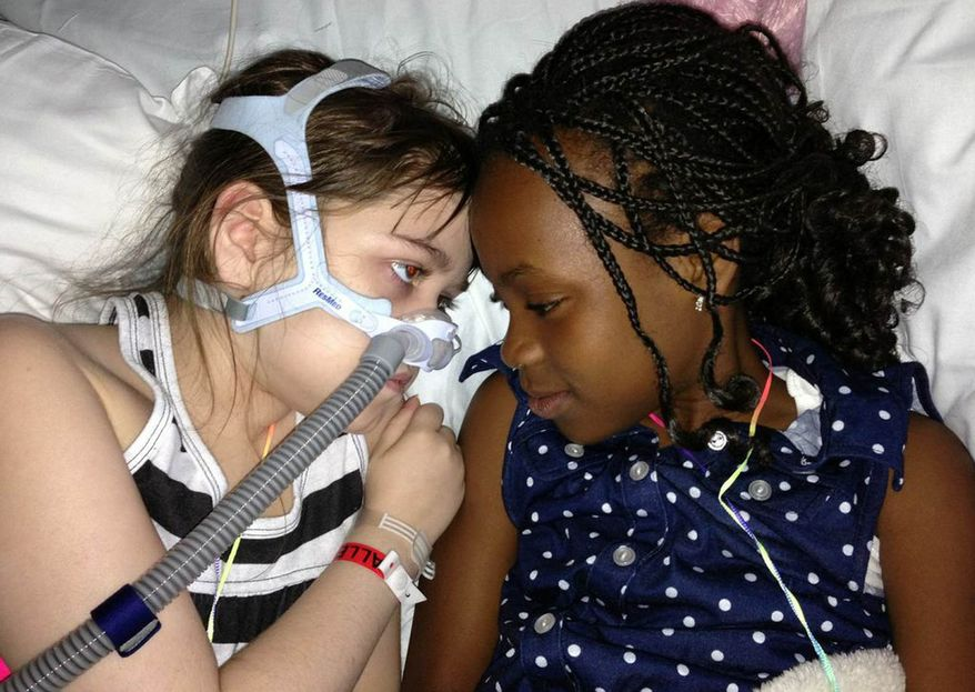 ** FILE ** In this May 30, 2013, file photo provided by the Murnaghan family, Sarah Murnaghan, left, lies in her hospital bed next to adopted sister Ella on the 100th day of her stay in Children's Hospital of Philadelphia. A federal judge in Philadelphia has made the dying 10-year-old eligible to seek donor lungs from an adult transplant list. (AP Photo/Murnaghan Family, File)