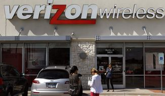 ** FILE ** Customers walk into a Verizon Wireless store in Dallas on Wednesday, Oct. 17, 2012. (AP Photo/LM Otero)
