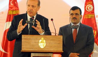 Turkish Prime Minister Recep Tayyip Erdogan gestures during a joint press conference held with Tunisian Prime Minister Prime Minister Ali Larayedh, right, at the palace hotel in Gammarth, north of Tunis, Tunisia, Thursday, June 6, 2013. (AP Photo/Hassene Dridi)