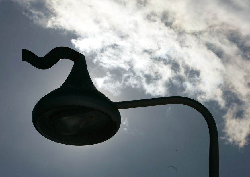**FILE** A street light shaped like a Hershey Kiss candy is silhouetted along the street in Hershey, Pa., on Feb. 15, 2007. (Associated Press)