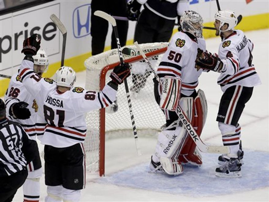 Chicago Blackhawks' Michal Handzus, Marian Hossa, goalie Corey Crawford, and Niklas Hjalmarsson, fromleft, celebrate a 3-2 win against the Los Angeles Kings in Game 4 of the NHL hockey Stanley Cup playoffs Western Conference finals, in Los Angeles on Thursday, June 6, 2013. (AP Photo/Chris Carlson)