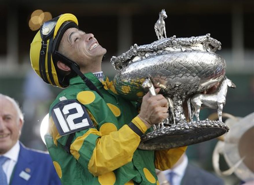 Jockey Mike Smith holds the Belmont Stakes trophy in the winner's circle after riding Palace Malice to win the race at Belmont Park in Elmont, N.Y., Saturday, June 8, 2013. (AP Photo/Seth Wenig)