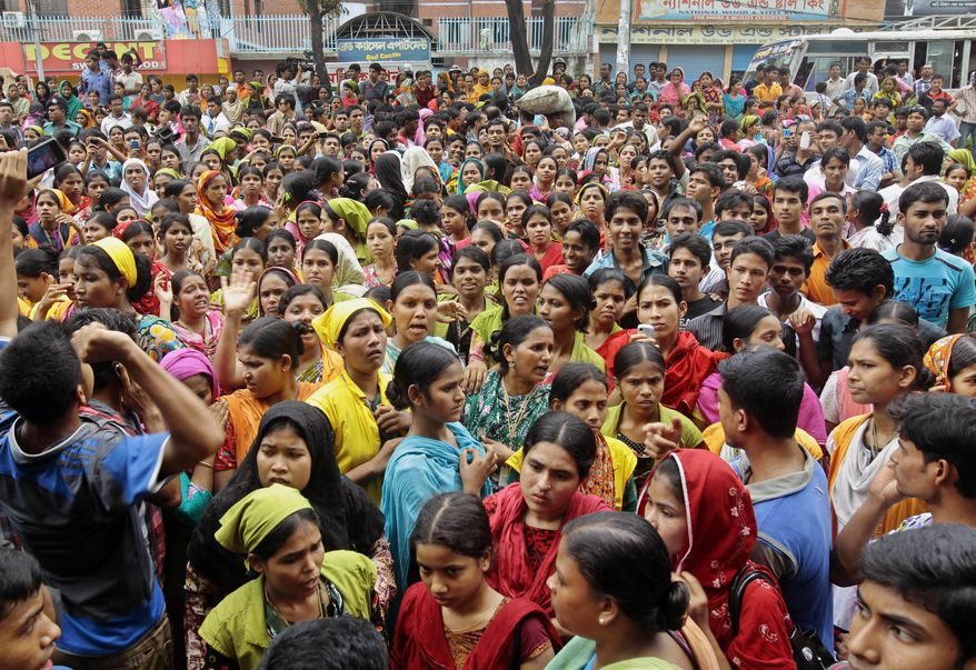 Bangladeshis gather during a demonstration by garment workers in Dhaka, Bangladesh, the capital, on Monday, May 27, 2013, to demand better working conditions and an increase in pay. (AP Photo/A.M. Ahad)