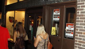 **FILE** Students, residents and visitors to Oxford, Miss., walk to various night spots around the town square on Sept. 18, 2010. A prominent sign reminds drinkers that a designated driver program is available for them. (Associated Press)