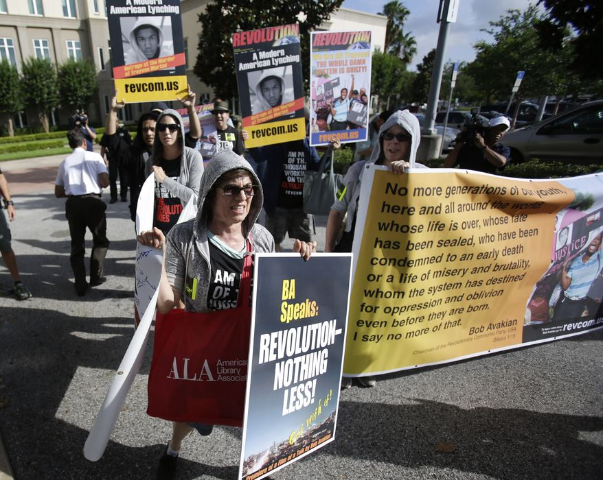 Members of the Revolutionary Communist Party, USA, demonstrate outside the Seminole County Courthouse in Sanford, Fla., on Monday, June 10, 2013, the first day of trial for George Zimmerman, who is charged with second-degree murder in the 2012 shooting death of Trayvon Martin. (AP Photo/John Raoux)