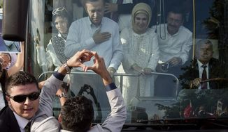 A man makes a heart shaped sign to Turkish Prime Minister Recep Tayyip Erdogan and his wife Emine to show support after his arrival in Ankara, Turkey, Sunday, June 9, 2013. (AP Photo/Vadim Ghirda)