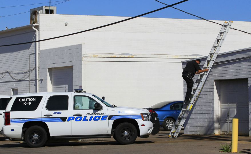 **FILE** Police in Chandler, Ariz., respond to a report of copper theft from a shopping plaza roof on Jan. 18, 2012. (Associated Press)