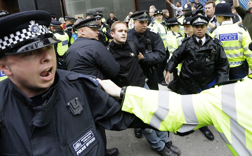 A demonstrator is taken to a police vehicle after he was detained during a protest in London on Tuesday, June 11, 2013. The protesters were railing against the G-8 summit in Northern Ireland next week. (AP Photo/Alastair Grant)