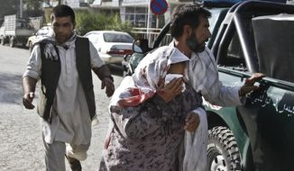 Afghan men rush a wounded woman to receive treatment, after a suicide car bomber struck outside the Afghan Supreme Court in Kabul, Afghanistan, Tuesday, June 11, 2013. (AP Photo/Ahmad Jamshid)