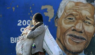 ** FILE ** Thabiso Ndandwe walks in front of a mural of former South African President Nelson Mandela in a Soweto township, in Johannesburg, South Africa, Monday, June 10, 2013. Mandela was in serious but stable condition in a Pretoria hospital for the third day Monday with a recurring lung infection. (AP Photo/Themba Hadebe)