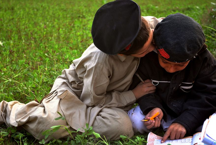Children playfully work on their homework after school. They sit in the fields in the evening near their house in a village near Peshawar. Photo / Shah Jehan