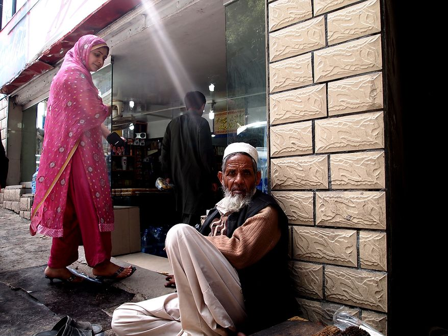 In the famous summer resort of Murree, an old man sits at the door of a shop at the mall waiting for someone to give him money. The woman entering the shop wants to give him money, but he is looking into the camera to get his photo taken. Photo / Rizwan Bhittani