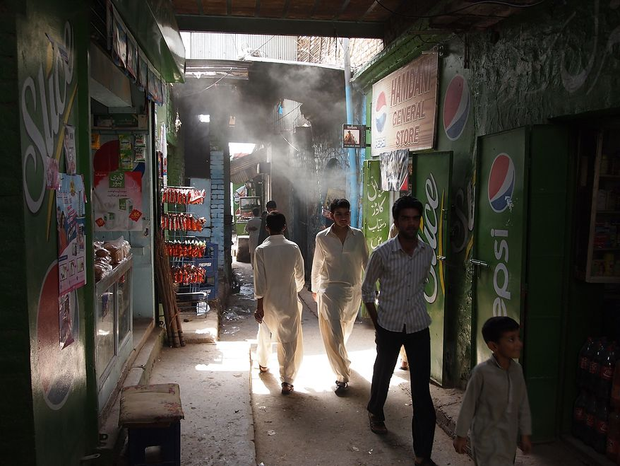 Men pass through a busy market of Saidpur village in Islamabad, where the locals buy their daily vegetables and fruits. People greet the shopkeepers as they continue on their way. The look on the boy's face as he gazes at the shop is pleasing. Photo / Seba Rehman