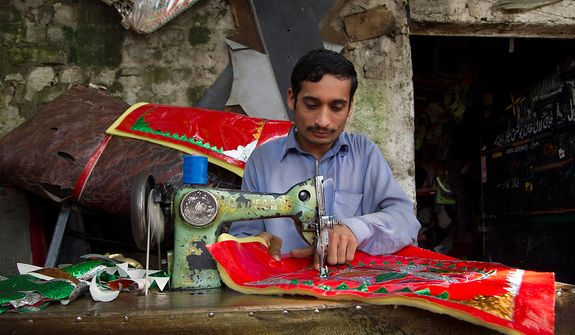 A young man stitches decorative seat covers and curtains at the truck art market in Rawalpindi, where he works at his master's shop for more than twelve hours a day. Photo / Noor Za Din