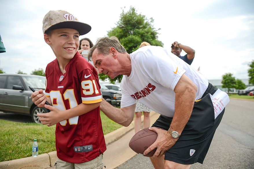 Washington Redskins head coach Mike Shanahan signs the shirt of Andrew Christopher, 9, of Fredericksburg, Md., at mini camp at Redskins Park, Ashburn, Md., Tuesday, June 11, 2013. (Andrew Harnik/The Washington Times)