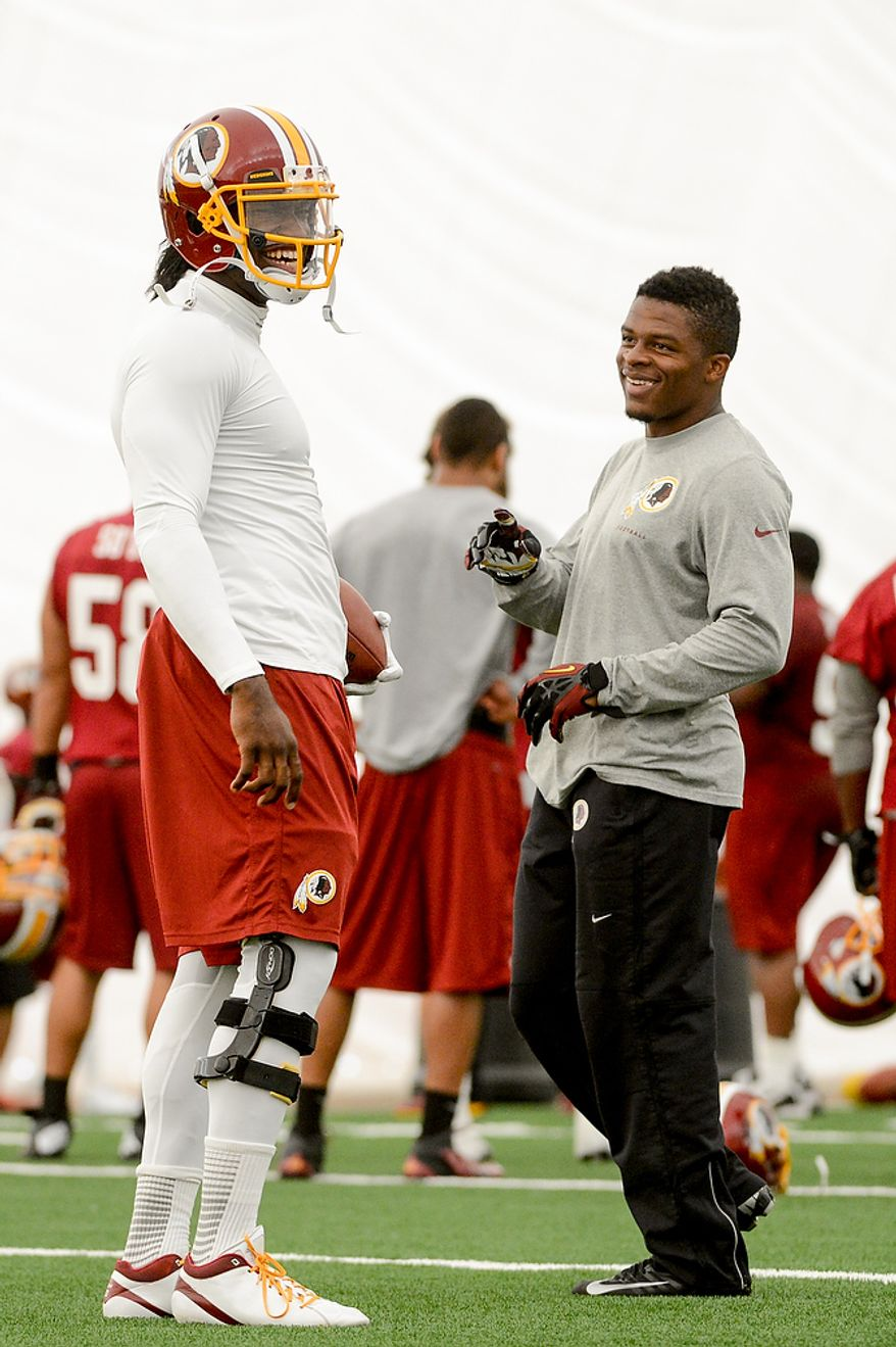 Washington Redskins quarterback Robert Griffin III (10), left, and running back Chris Thompson (35), right, share a laugh together on the field during mini camp at Redskins Park, Ashburn, Md., Tuesday, June 11, 2013. (Andrew Harnik/The Washington Times)