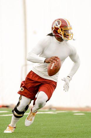 Washington Redskins quarterback Robert Griffin III (10) practices throwing while scrambling at mini camp at Redskins Park, Ashburn, Md., Tuesday, June 11, 2013. (Andrew Harnik/The Washington Times)