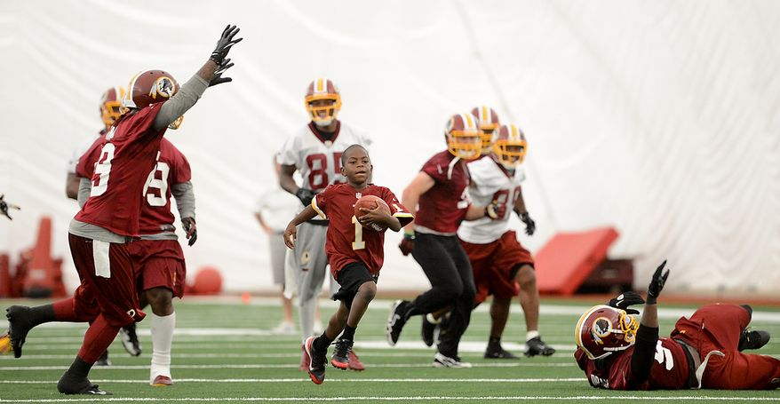 Washington Redskins players try to tackle Lateef Brock, of Clinton, Md. who was visiting the Redskins with the Make a Wish foundation as he gets to run for a touchdown after practice during mini camp at Redskins Park, Ashburn, Md., Tuesday, June 11, 2013. (Andrew Harnik/The Washington Times)