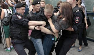 Police officers detain gay rights activists as they gathered near the State Duma, Russia's lower parliament chamber, in Moscow, Russia, Tuesday, June 11, 2013. (AP Photo/Ivan Sekretarev)